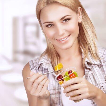 ensalada de frutas: Retrato de la hermosa chica rubia para el desayuno con el placer de comer ensalada de frutas, que serpentea en casa, disfrutando de una alimentación sana Foto de archivo