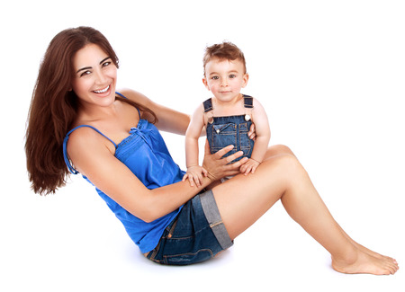 infant: Cheerful young mother with her cute little son sitting on the floor and playing in the studio, isolated on white background, happy family together Stock Photo