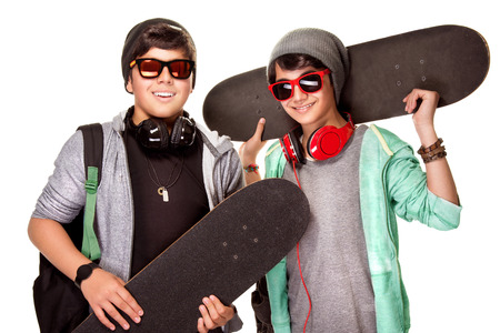 people listening: Portrait of two happy teen boys with skateboards isolated on white background, cool trendy look, active urban lifestyle of youth