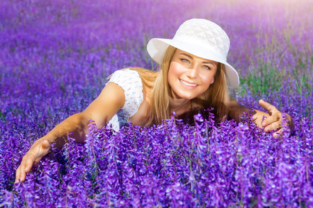 nature beauty: Beautiful woman in sunny day wearing sun hat and sitting in fresh purple flower field, enjoying beauty of nature Stock Photo