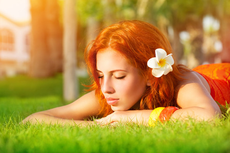 red hair girl: Portrait of cute calm girl lying down on fresh green grass with franjipani flower in red hair, dreamy closing eyes, enjoying day spa on luxury beach resort Stock Photo