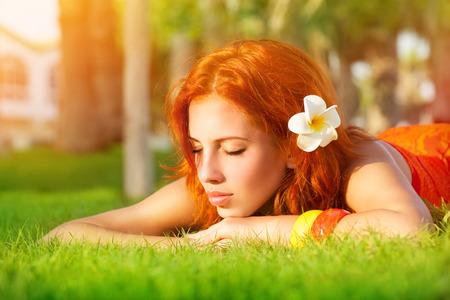 closing eyes: Portrait of cute calm girl lying down on fresh green grass with franjipani flower in red hair, dreamy closing eyes, enjoying day spa on luxury beach resort Stock Photo