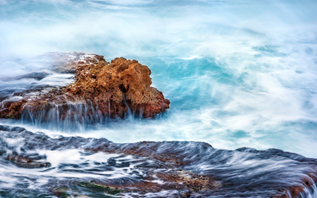 slow motion: Beautiful rock in the sea, turquoise water flows over cliff at stormy weather day, slow motion scene, beauty of mother nature