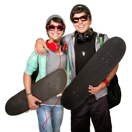 escucha activa: Dos patinadores felices escuchando m�sica en los auriculares usar ropa de moda urbana y gafas de sol aisladas sobre fondo blanco, la vida moderna activa de los j�venes
