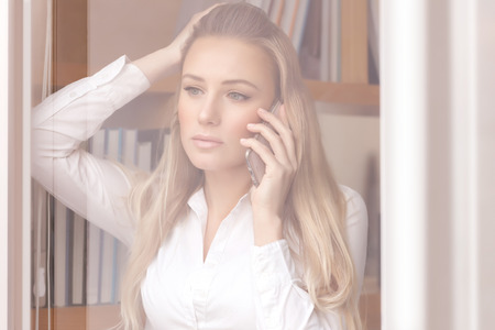disquieted: Portrait of beautiful worried business woman standing near windows in the office and discussing some problems on the phone Stock Photo