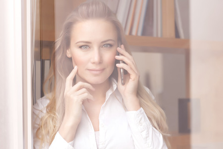 Portrait of a beautiful confident business woman on the phone, standing near windows at the office, young female at work Banque d'images