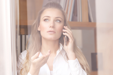 disquieted: Portrait of beautiful serious business woman speaking on the phone and looking through the window, explaining something to business partner Stock Photo