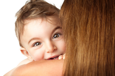 peekaboo: Baby boy playing peek-a-boo, cute little child looks out of his mothers shoulder, isolated on white background, happy family having fun