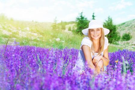 campo de flores: Mujer feliz linda que se divierte en el campo de lavanda, disfrutando de las flores púrpuras suaves frescas, con un gasto placer días soleados de primavera al aire libre