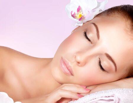 ojos cerrados: Primer retrato de una mujer dulce hermosa con los ojos cerrados de relax en mesa de masaje en el spa salón, estilo de vida saludable, tratamientos de belleza Foto de archivo
