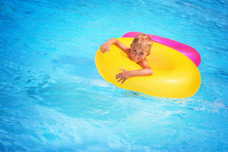 rubber ring: Cute happy little boy having fun in swimming pool, floating in blue refreshing water with big green rubber ring, active summer vacation on the beach