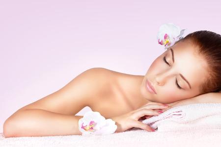 Retrato de una mujer dulce hermosa con los ojos cerrados de relax en mesa de masaje en el spa salón, estilo de vida saludable, tratamientos de belleza