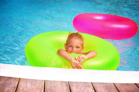 rubber ring: Cute happy little boy having fun in swimming pool, with pleasure floating on big green rubber ring, spending summer holidays on beach resort Stock Photo