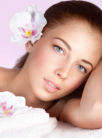 spa flower: Closeup portrait of a beautiful woman with orchid flower in hair, lying down on massage table, spending wonderful day at spa, happy healthy lifestyle