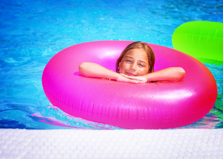 rubber ring: Cute happy little girl having fun in swimming pool, with pleasure floating on big pink rubber ring, spending summer holidays on beach resort