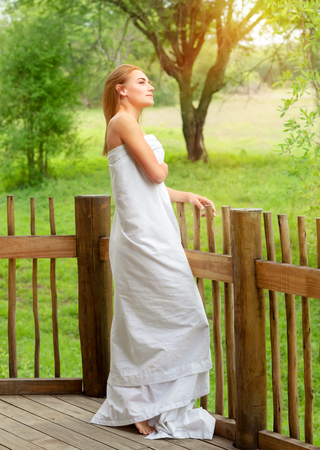 people relax: Gentle woman wrapped in the bedsheet standing on terrace and enjoying fresh summer nature, relaxation on spa resort Stock Photo