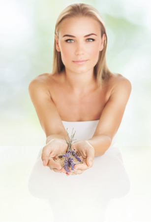 Woman at beauty salon, beautiful female at spa holds lavender flowers and bath salt, aromatherapy herbal anti-stress treatment for helth of mind and soul, body skin face and hair care, selective focus Stock Photo