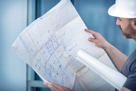 Industrial workers: Portrait of an architect builder studying layout plan of the rooms, serious civil engineer working with documents on construction site, building and home renovation, professional foreman at work