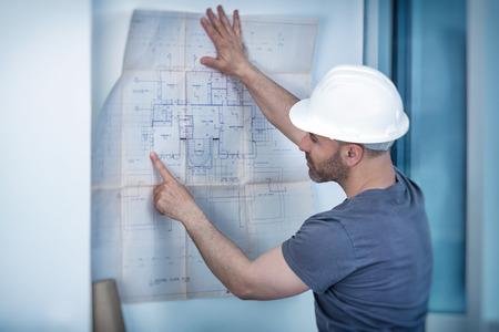 ingeniero civil: Retrato de un constructor del arquitecto que estudia plan de distribución de las habitaciones, seria ingeniero civil que trabaja con los documentos en el sitio de construcción, la construcción y rehabilitación de viviendas, capataz profesional en el trabajo