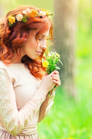 Portret van een mooie zachte vrouw in een bos, vrouwelijke genieten van aroma van een klein boeket van wilde bloemen, schoonheid van de lente de natuur Stockfoto