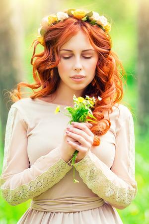 ojos verdes: Retrato de una hermosa muchacha romántica con los ojos cerrados disfrutando de un aroma de flores silvestres suaves en el parque de la primavera, mirada sensual de la manera de la ninfa de los bosques Foto de archivo