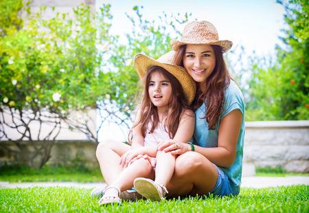 mama e hija: Familia feliz en el jardín, bella madre con su pequeña hija linda que se sienta en la hierba verde fresca en el patio trasero, con el tiempo el gasto placer juntos Foto de archivo