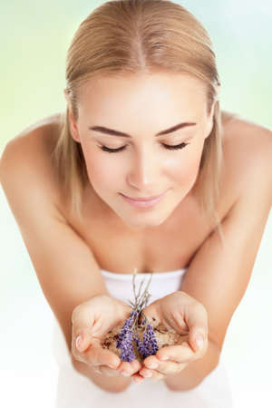 natural face: Portrait of a woman at spa beauty salon, holds in hands lavender and sea salt, enjoying aromatherapy herbal anti-stress treatment for health of mind and soul, body skin face and hair care