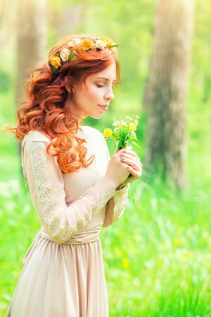 nature beauty: Portrait of a beautiful gentle woman in a forest, female enjoying aroma of a little bouquet of wild flowers, beauty of spring nature