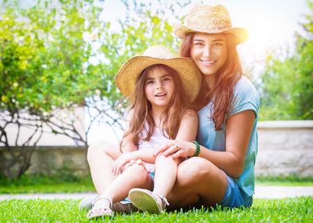 family garden: Happy family in the garden, beautiful mother with her little cute daughter sitting on fresh green grass on a backyard, with pleasure spending time together