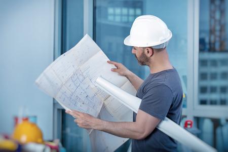 Ritratto di un costruttore architetto Studio di programma della disposizione delle stanze, grave ingegnere civile che lavora con i documenti in cantiere, la costruzione e ristrutturazione casa, caposquadra professionale sul posto di lavoro