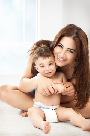home life: Cheerful young mother with her cute little son playing at home, with pleasure spending time together, happy family life Stock Photo