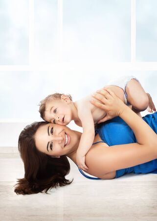family life: Cheerful joyful mother playing with her adorable son, lying down on the floor at home, enjoying motherhood, happy family life