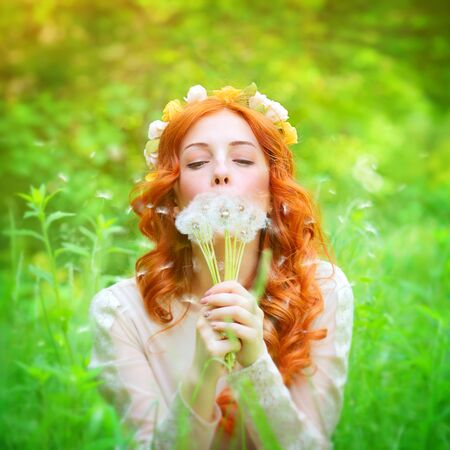 pretty hair: Closeup portrait of a beautiful dreamy female holding in hands dandelion flowers and with closed eyes blowing on it, enjoying beauty of spring nature