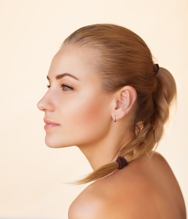 white back: Profile portrait of a beautiful sensual woman with braid hairstyle over beige background, gentle natural makeup, natural beauty of a woman face with a healthy skin