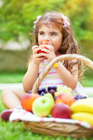 eating fruits: Portrait of a cute little girl sitting on the green grass field in a park and with pleasure eating tasty juicy apple, healthy babies nutrition