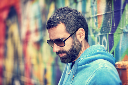man with beard: Closeup portrait of handsome man with stylish beard and sunglasses, standing over colorful city wall background, fashion street look, urban lifestyle