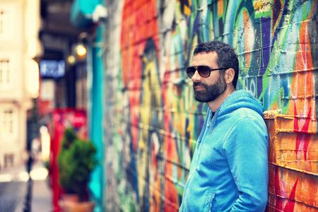 street life: Handsome man wearing stylish sunglasses, standing near beautiful colorful wall on the street, fashion urban look, city life Stock Photo