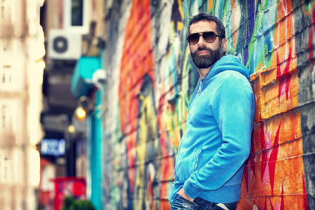 Handsome man wearing stylish sunglasses, standing near beautiful colorful wall on the street, fashion urban look, city life Foto de archivo