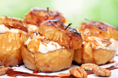 delicious food: Closeup photo of a tasty baked apples stuffed with cream honey and nuts, healthy nutrition, delicious sweet food, gorgeous fruit dessert flavored with cinnamon