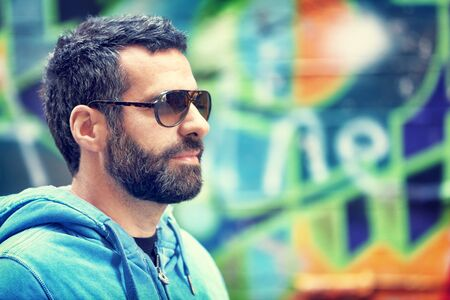 beard man: Closeup portrait of handsome man with stylish beard and sunglasses, standing over colorful city wall background, fashion street look, urban lifestyle