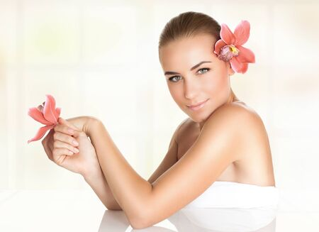 dayspa: Pretty girl with orchid flowers in the hair and hand enjoying dayspa, body care, healthy lifestyle, beauty treatment in a spa salon, relaxation on massage table