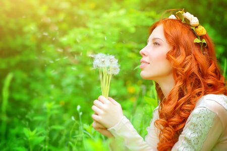 pretty hair: Portrait of a beautiful girl wearing floral wreath, enjoying spring grass field, holding in hands bouquet of a dandelion flowers and daydreaming about a wish Stock Photo
