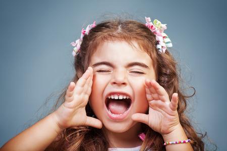 Portret van een schattige kleine baby meisje gillen, stout kind schreeuwen, het uiten van emoties, speels kind enthousiast over en het maken van gezichten