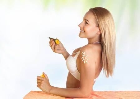 beautiful body: Beautiful young girl using sunscreen on the beach to protect her skin from sunburn, healthy sunbathing, woman enjoying happy summer vacation Stock Photo