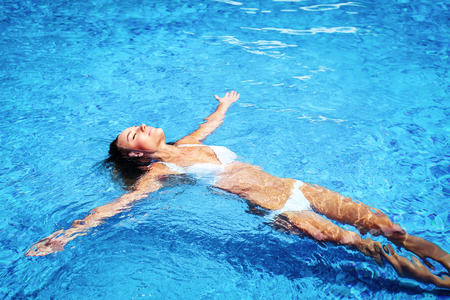 Pretty girl in swimming pool, relaxing in cold refreshing water on hot summer day, enjoying life, spending holidays on the beach resort