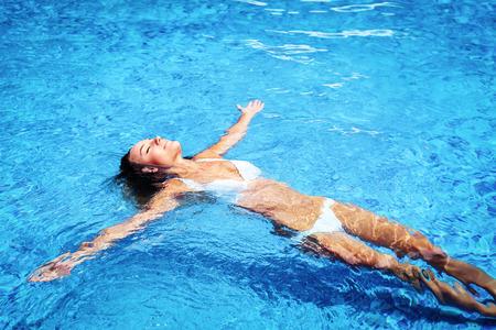 Mooi meisje in het zwembad, ontspannen in het koude verfrissende water op hete zomerdag, genieten van het leven, een vakantie op het strand vakantieoord Stockfoto