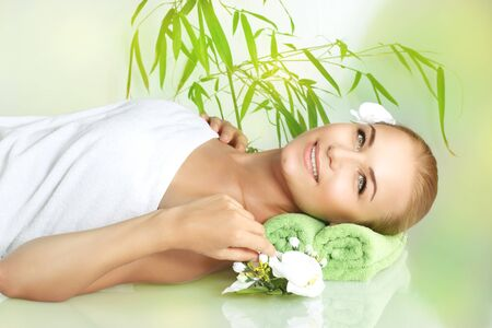 mimos: Retrato de una mujer sonriente feliz que se acuesta en una mesa de masaje en el spa de lujo del sal�n, mujer joven disfrutando de un tratamiento de belleza y cuidado del cuerpo