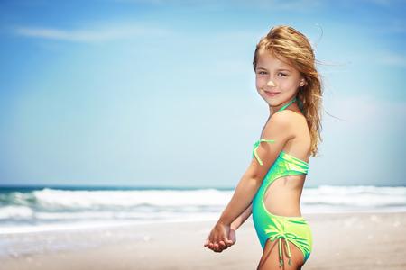 petite fille maillot de bain: Portrait d'une petite fille mignonne sur une plage, passer des vacances dans un camp d'été sur un bord de mer, l'enfance heureuse et saine