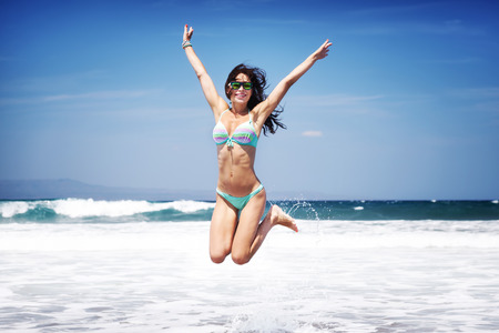 Happy joyful woman having fun on a beach, with pleasure jumping on a seashore, enjoying summer vacation on a tropical resort