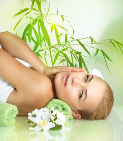 dayspa: Portrait of a beautiful gentle girl relaxing on a massage table, medical therapy in a beauty salon, healthy lifestyle, enjoying dayspa on a luxury spa resort Stock Photo